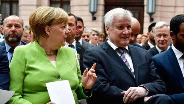 Kanclerz Niemiec Angela Merkel i minister spraw wewnętrznych Niemiec Horst Seehofer podczas Światowego Dnia Uchodźcy w Berlinie - Sputnik Polska
