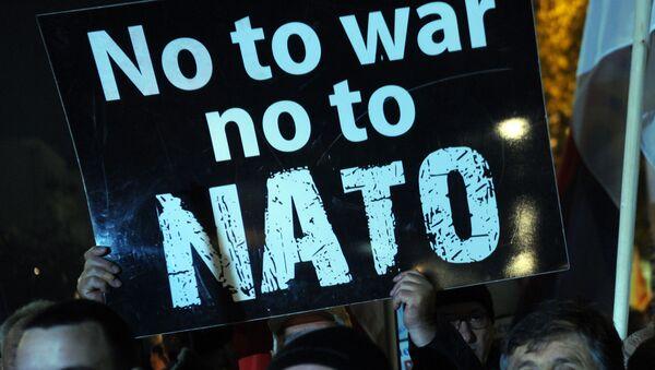 Protestujący trzymające plakat z napisem Nie wojnie, nie NATO w Podgoricy - Sputnik Polska