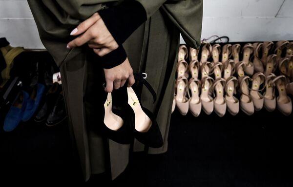Modelka trzyma swoje buty czekając wyjścia na wybieg podczas Tygodnia Mody Islamskiej w Kuala Lumpurze - Sputnik Polska