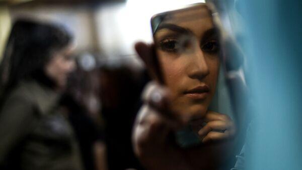 Modelka sprawdza makijaż przed wyjściem na wybieg podczas Tygodnia Mody Islamskiej w Kuala Lumpurze - Sputnik Polska