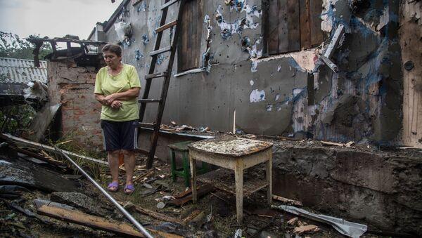 Kobieta obok zniszczonego domu po ostrzałach w mieście Złote w obwodzie ługańskim - Sputnik Polska
