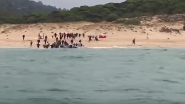 Migranci rozbiegają się po plaży - Sputnik Polska