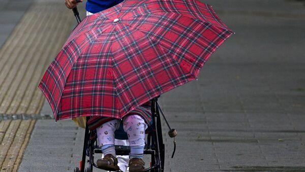 Dziecko pod parasolką w wózku w Pekinie - Sputnik Polska