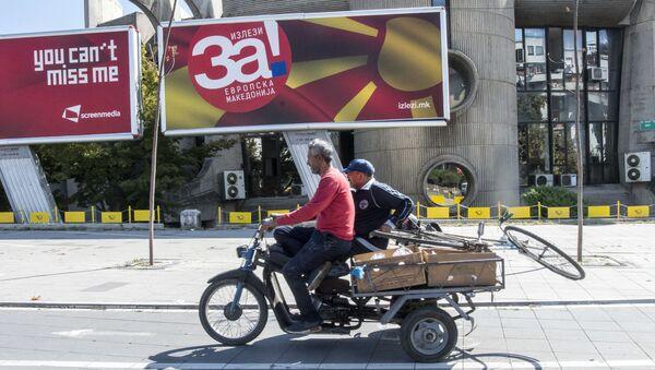 Mężczyzna przejeżdża motorowerem obok billboardu z reklamą referendum - Sputnik Polska
