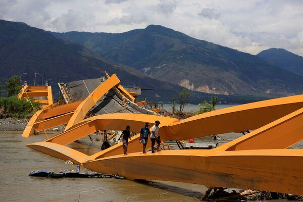 Ludzie idą po zniszczonym w wyniku trzęsienia ziemi moście w Palu na wyspie Sulawesi, Indonezja - Sputnik Polska