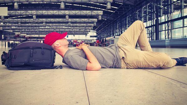 Mężczyzna leży na podłodze w oczekiwaniu na lot - Sputnik Polska