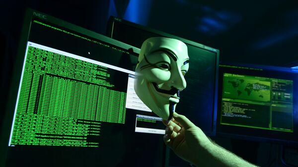 Maska Guya Fawkesa przed ekranami komputerów - Sputnik Polska