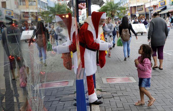 Święty Mikołaj częstuje dziewczynkę cukierkami, Brazylia - Sputnik Polska