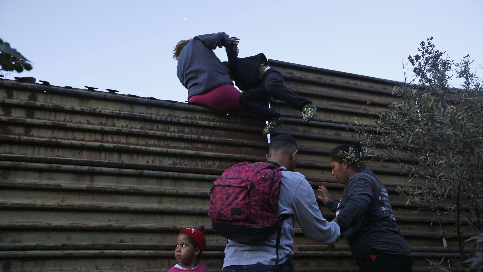 Migranci przechodzą przez mur na granicy USA i Meksyku - Sputnik Polska, 1920, 06.08.2021