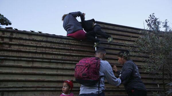 Migranci przechodzą przez mur na granicy USA i Meksyku - Sputnik Polska