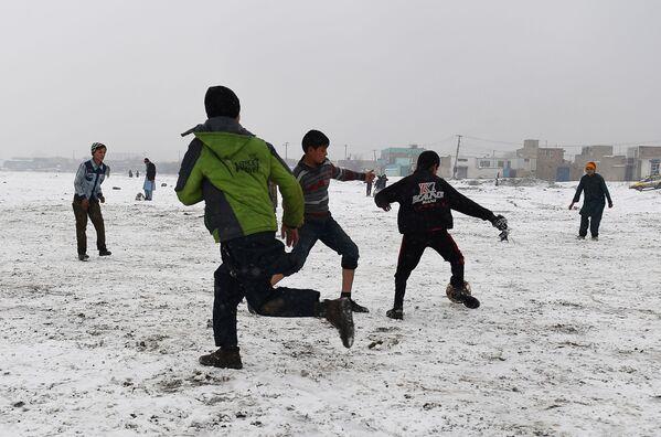 Dzieci grają w piłkę nożną po opadach śniegu w Kabulu - Sputnik Polska