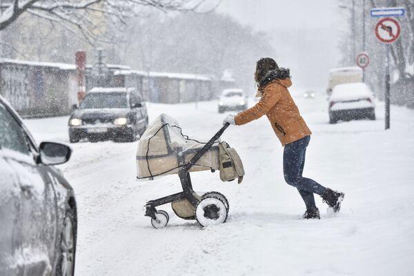 Kobieta z wózkiem na zaśnieżonej ulicy Bratysławy, Słowacja - Sputnik Polska