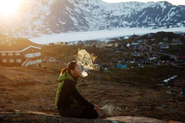 Młoda kobieta pali papierosa. Tasiilaq, Grenlandia - Sputnik Polska
