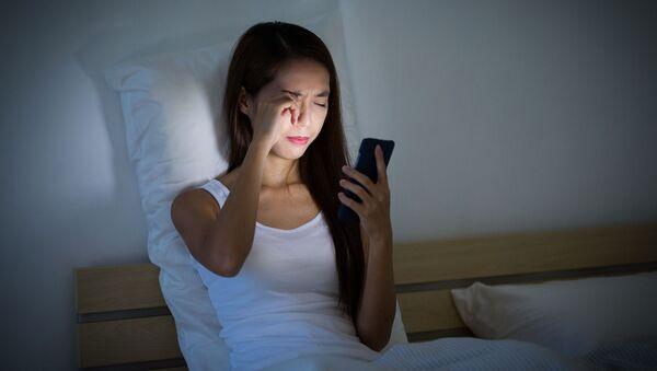 Dziewczyna z telefonem komórkowym w ręce w łóżku - Sputnik Polska