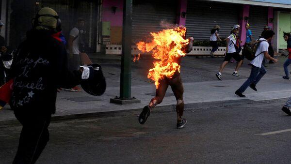 Mężczyzna objęty płomieniami biegnie ulicą w czasie masowych protestów przeciwko polityki Maduro w Wenezueli - Sputnik Polska