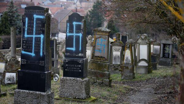 Nagrobki zbezczeszczone swastykami i antysemickimi napisami na cmentarzu żydowskim w gminie Quatzenheim we wschodniej Francji - Sputnik Polska